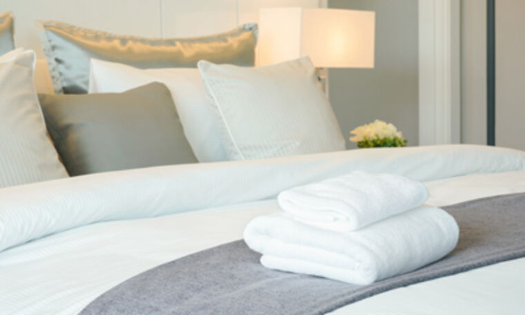 Close up of bed with folded towels at Amica senior living residence.