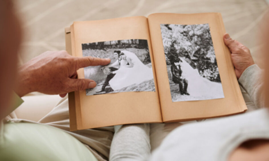 Two seniors looking at an old photo album at Amica senior retirement residence.