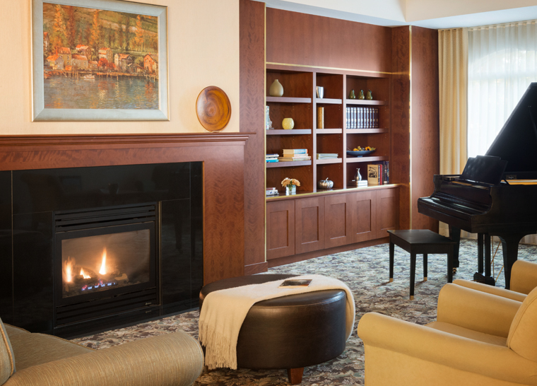 Fireside lounge with grand piano at Amica Newmarket senior living residence.
