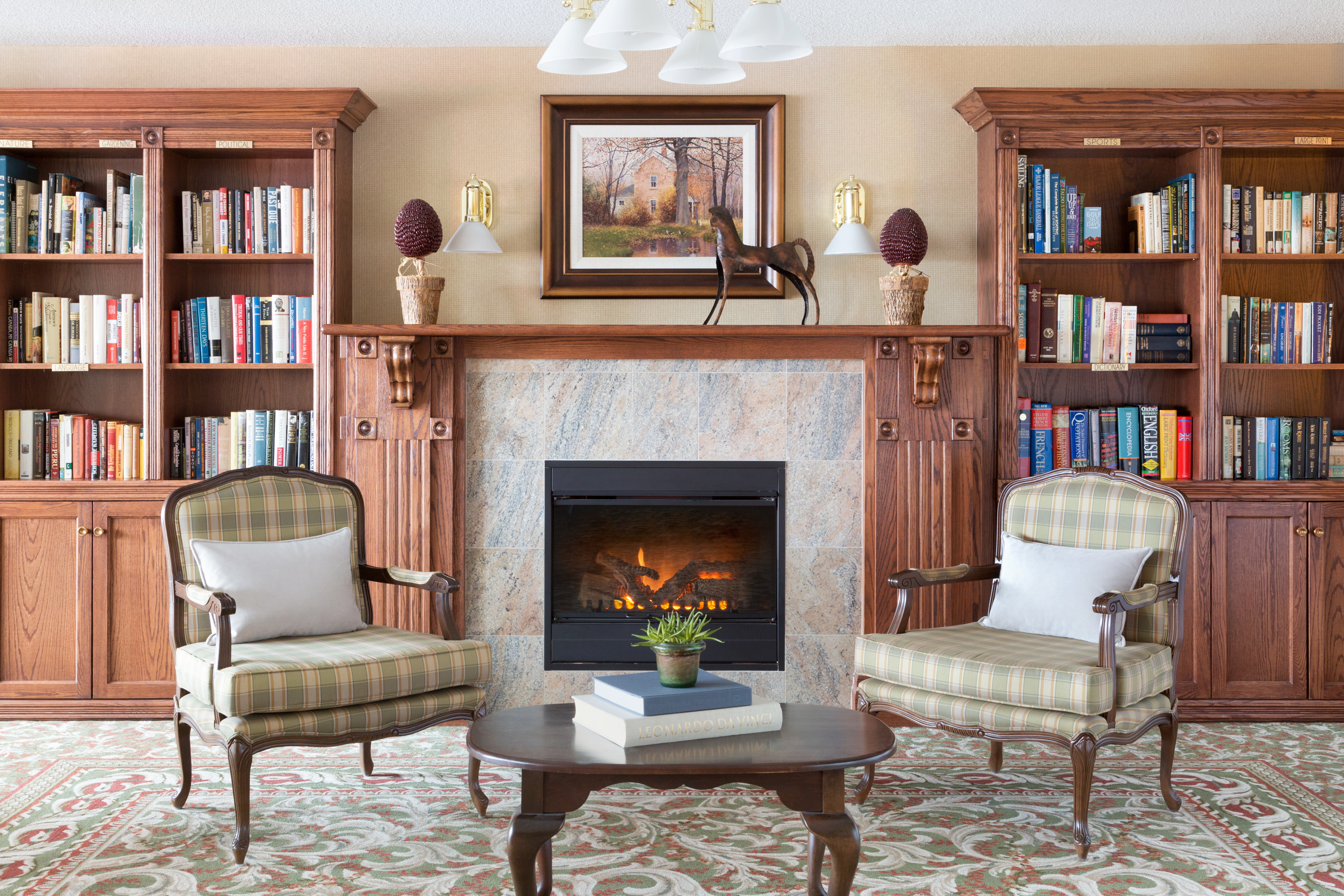 Library room with fireplace at Amica City Center senior living residence.