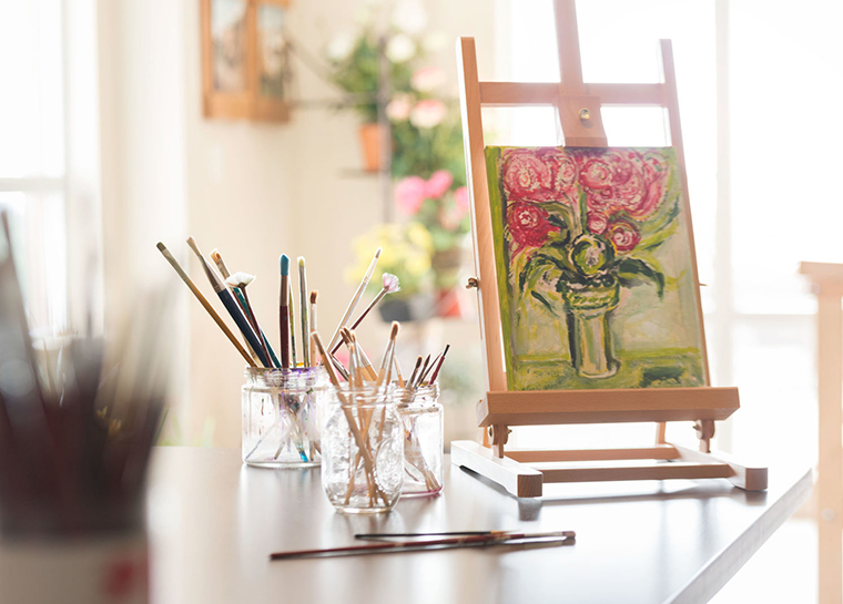 art on display with freshly used brushes in the craft kitchen
