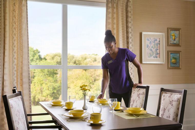 staff member setting the table in the Memory Care dining room at Amica Georgetown