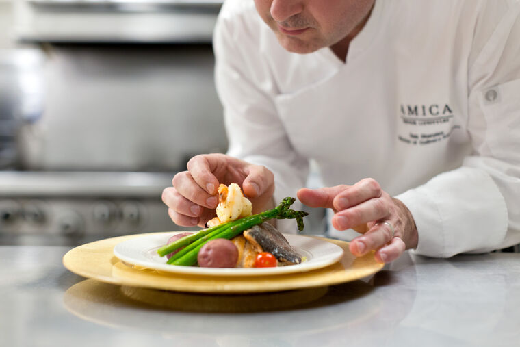 Chef garnishing a meal at Amica Edgemont Village