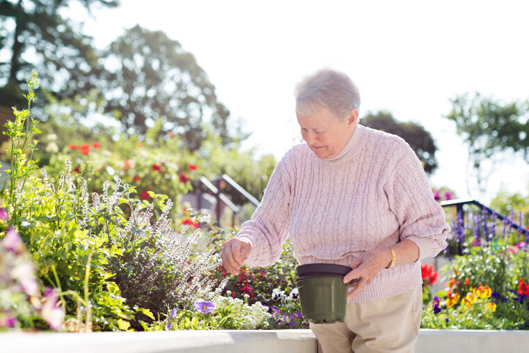 Senior tending the flowers in the garden at Amica On The Gorge