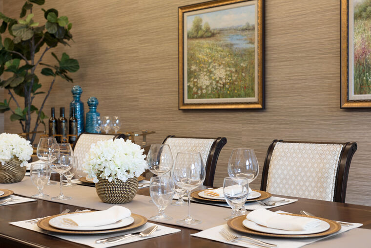 A private dining room including a dining table, glassware, cutlery and paintings on the wall.