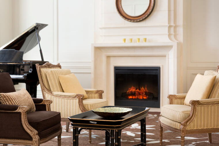 Lobby featuring the armchairs, piano and a fireside.