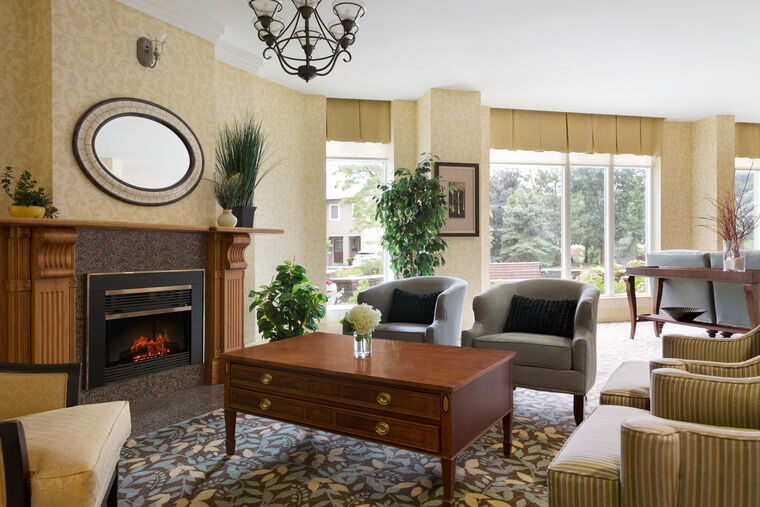 Fireside lounge featuring bright cozy space with armchairs around the coffee table and the fireside.