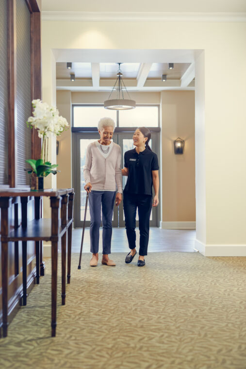 Female resident walking down hallway with support of cane and female caregiver