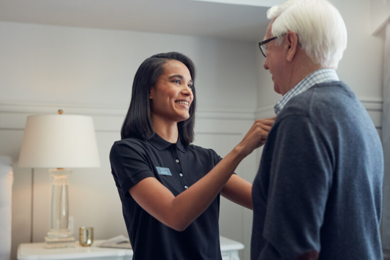 Female caregiver assisting male resident with shirt buttons in suite