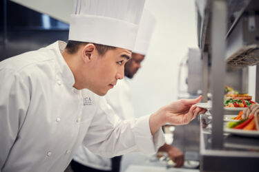 Amica Chef placing a plate of food on the pass in the back-of-house kitchen