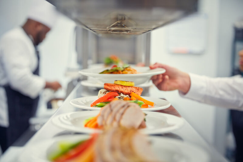 Assortment of plated meals on kitchen pass with chef in background