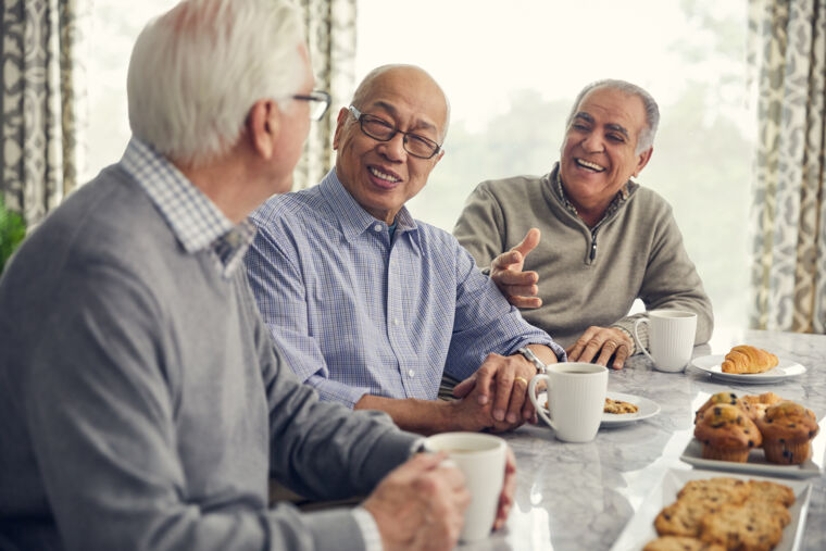 Three male residents socializing with coffee and assorted pastries at table