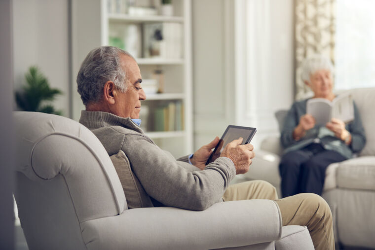 Male resident sitting in chair with iPad, across from female resident reading book on couch