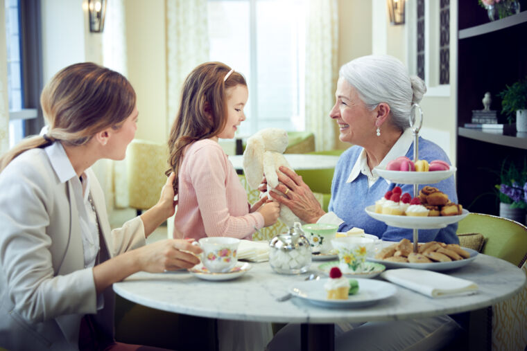 Female resident, adult daughter and granddaughter enjoying a tea party