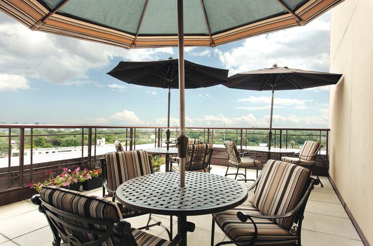 Amica Bayview Gardens outdoor patio tables with sun umbrellas