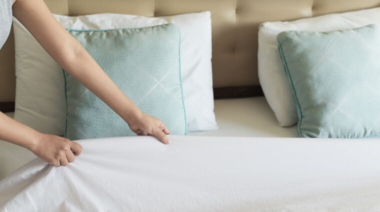 A housekeeper making the bed in a resident's suite