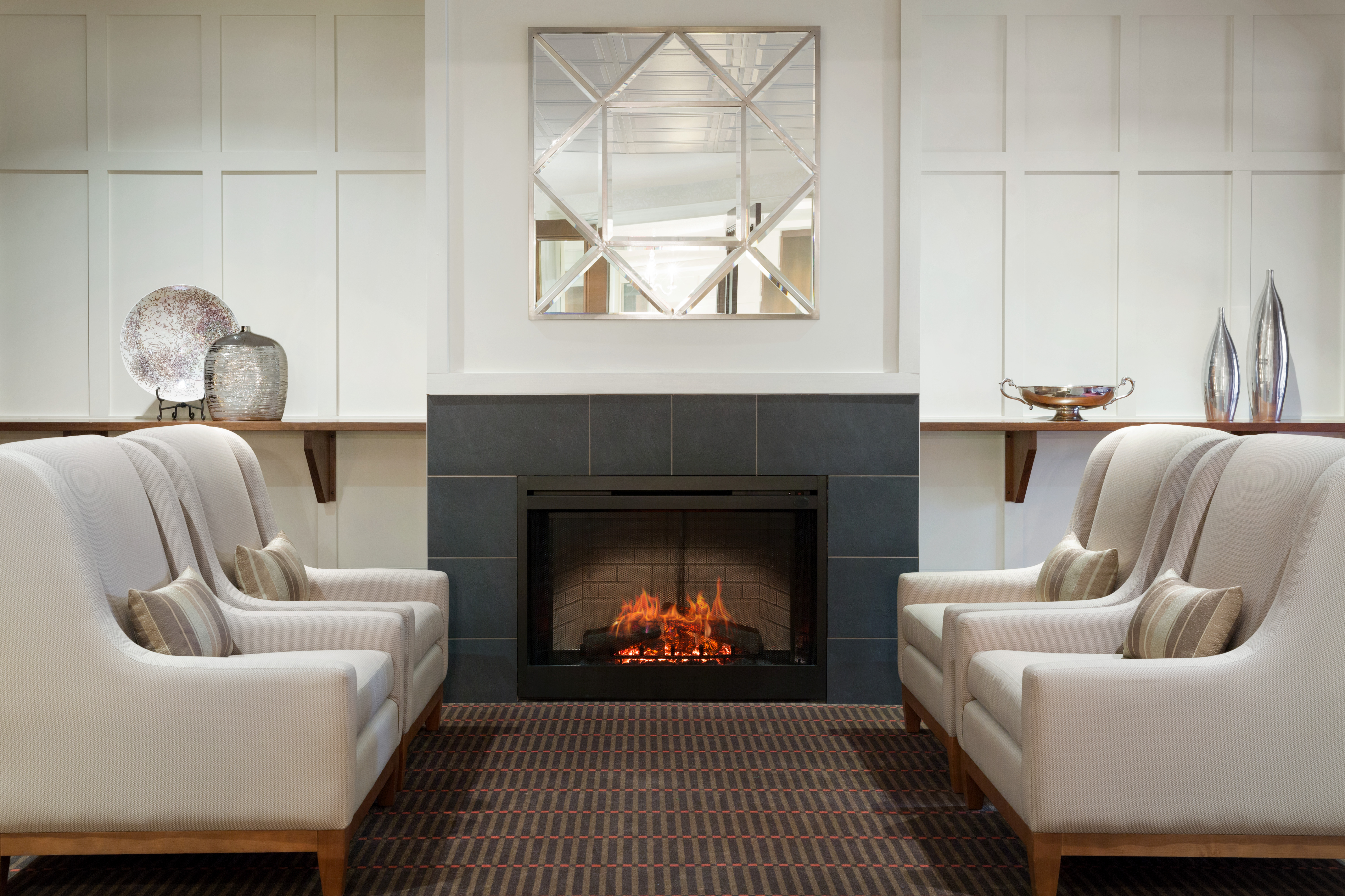 Amica London's Fireside Lounge: four beige armchairs facing one another next to a fireplace.