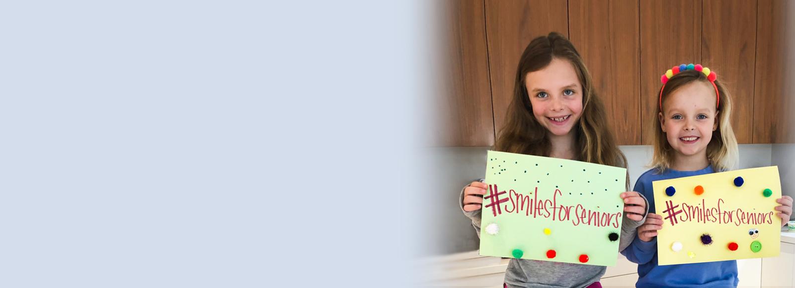 Kids holding #smilesforseniors signs