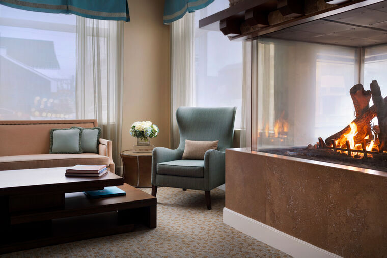 A corner of a lobby with armchairs and a fireplace at Amica Britannia.
