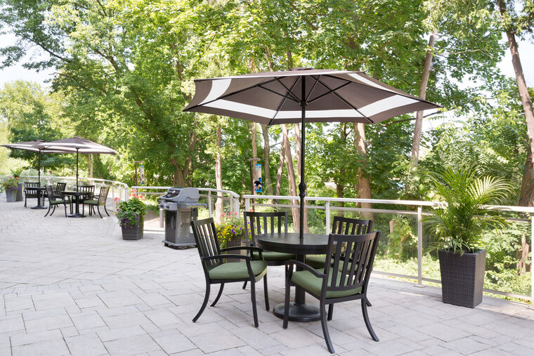 A spacious green patio of Amica Unionville with tables standing in the shade of patio umbrellas and a barbecue grill in the center.