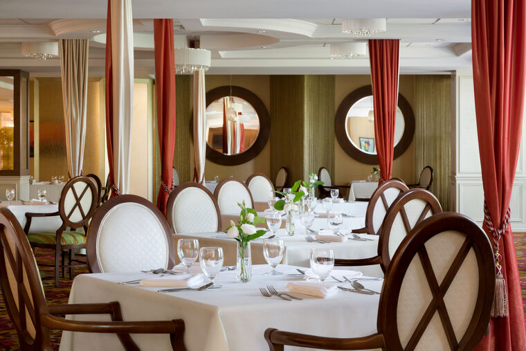 The main dining room of Amica Unionville is furnished with 4-person tables which are set to be served.