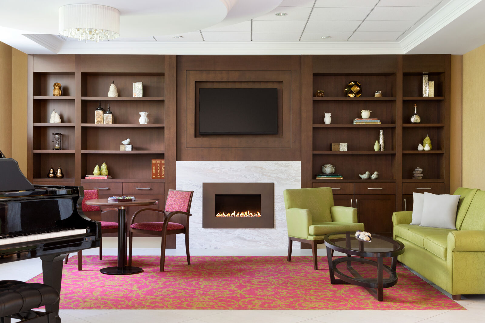 Seating area at Amica Unionville's Bistro: at the back there is a dark wooden closet with decorative elements on its shelves, a TV and a fireplace, and the room is furnished with couches, armchairs and a piano.