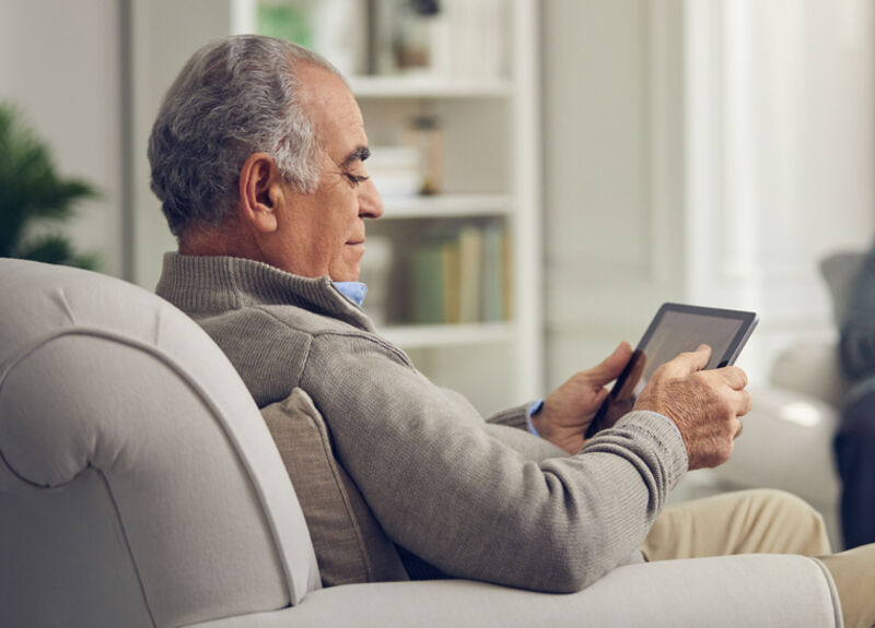 Male resident sitting in a comfortable chair using a tablet