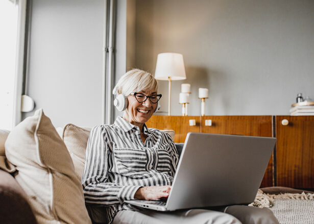 Senior woman is in her home using a laptop