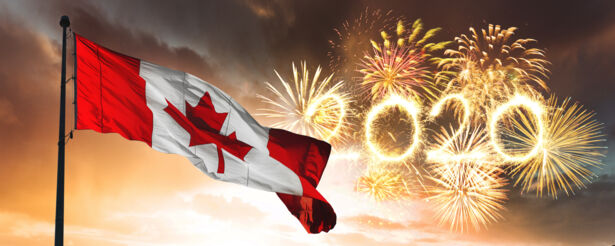 A Canadian flag flying in front of a sky with 2020 fireworks on display