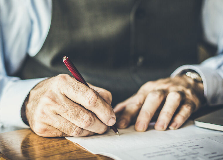 close-up shot of a senior's hands signing a legal document