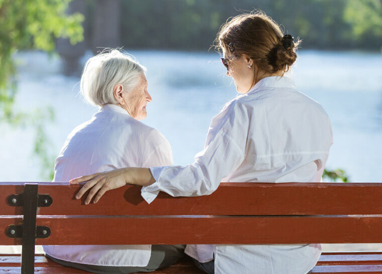 Senior and family member sitting on a bench