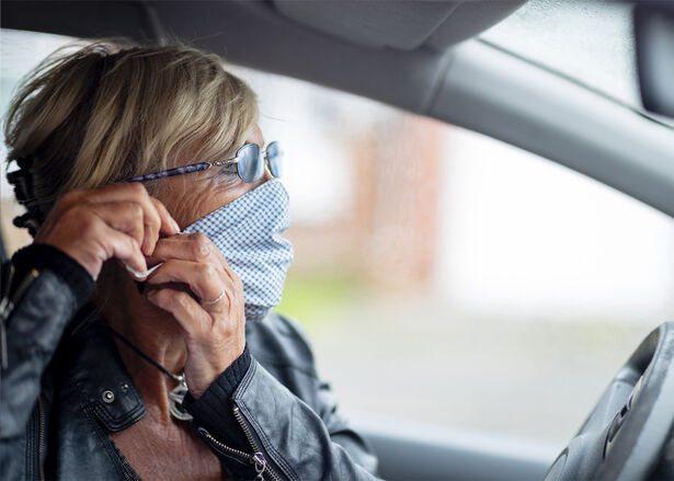 A senior woman wearing a protective face mask while sitting in her car.