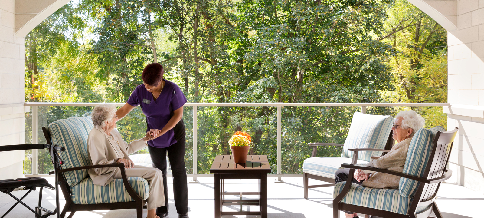 Two senior women and a caregiver are enjoying a bright sunny afternoon on the main floor terrace's couches.