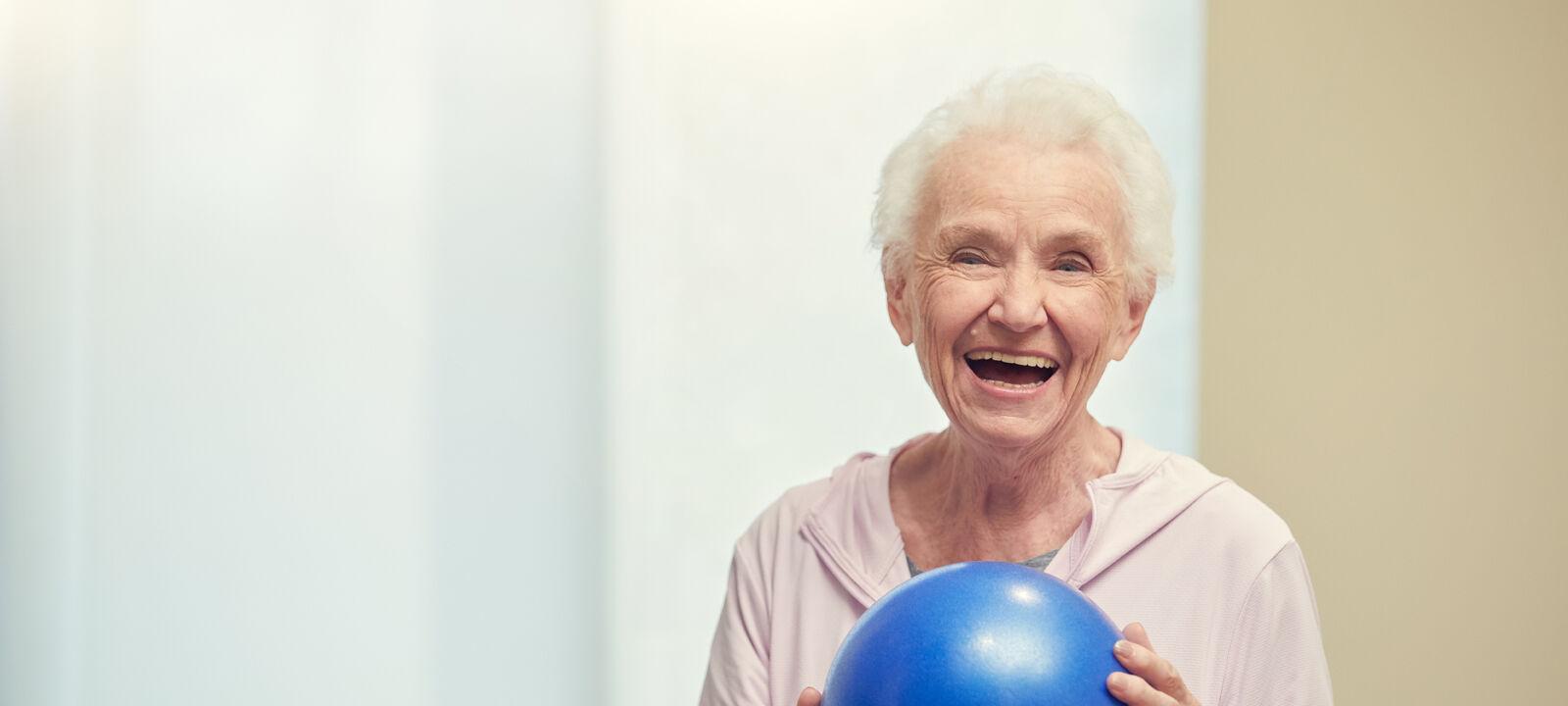 Female resident holding exercise ball
