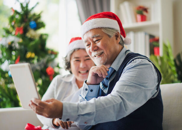 Senior man and woman using a tablet to video call with their family on Christmas day in a living room at home.