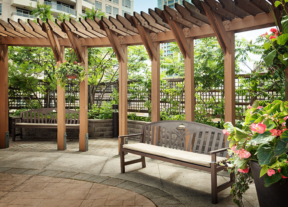 Amica Bayview Village senior living residence beautiful outdoor garden with bench.
