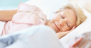 Senior woman with her eyes closed lying besides her husband in bed.