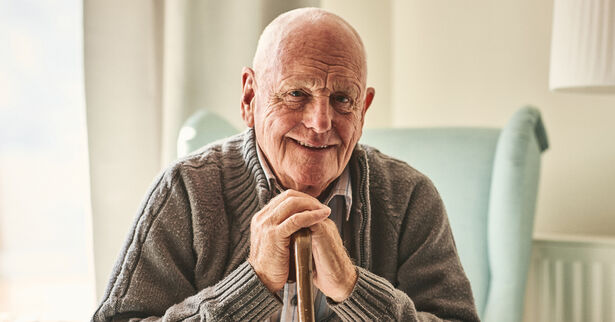 Portrait of happy senior man sitting at home with walking stick and smiling