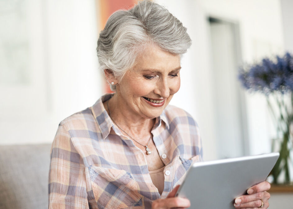 Shot of a happy mature woman using a tablet while relaxing in her lounge at home