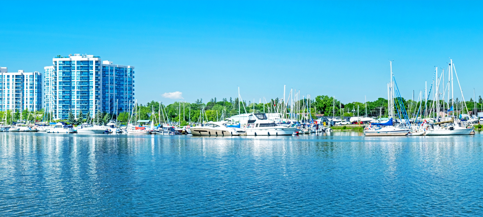 Reflections of a building and boats in the water of the Whitby Marina on Lake Ontario.