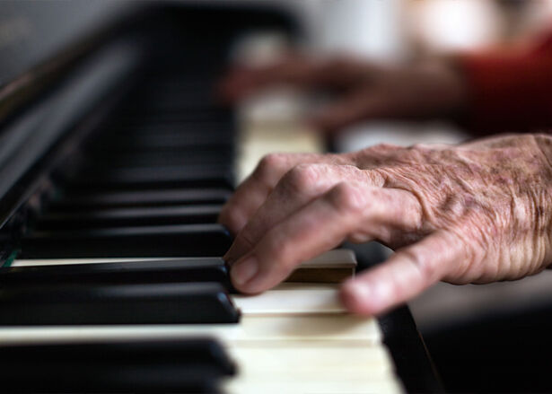 A senior person's hands play the piano.