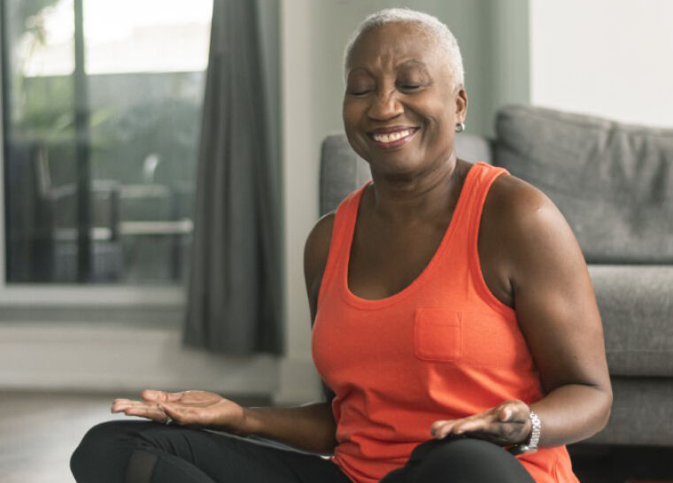 Senior woman wearing athletic wear sitting cross legged on the ground in a yoga pose while smiling