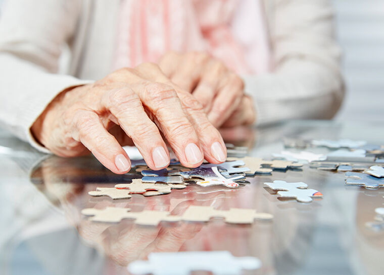 Close up shot of a senior lady working out a puzzle on the table
