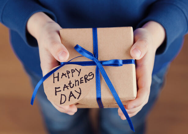 Children's hands holding a gift or present box with kraft paper and tied blue ribbon tag on Father's Day