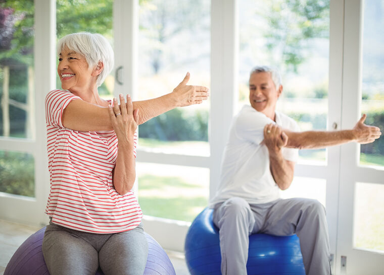 Senior woman and man smiling while stretching on exercise balls