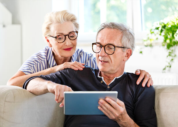 Senior man sitting on sofa in the living room at home and showing something on digital tablet his wife. Senior woman peeking on screen.