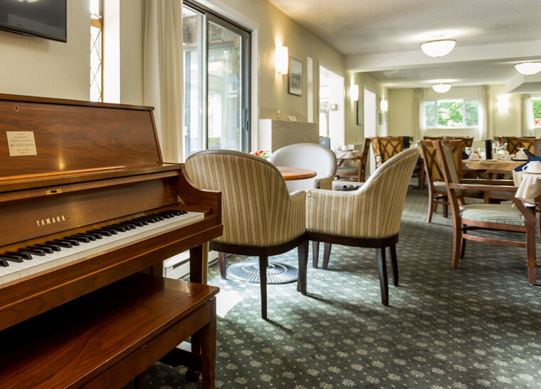 Dining room with piano at Amica Douglas House senior living residence.
