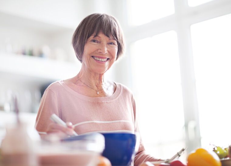 Portrait of beautiful elderly woman in kitchen looking at camera smiling