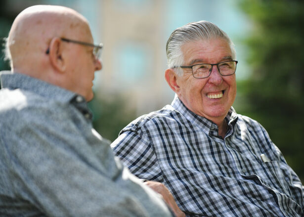 Two elderly men sitting on a park bench laughing and smiling