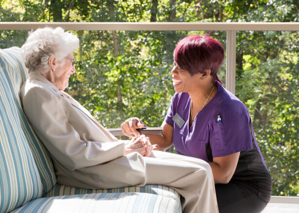An Amica Team Member kneeling down to speak with a resident sitting in a patio char outdoors